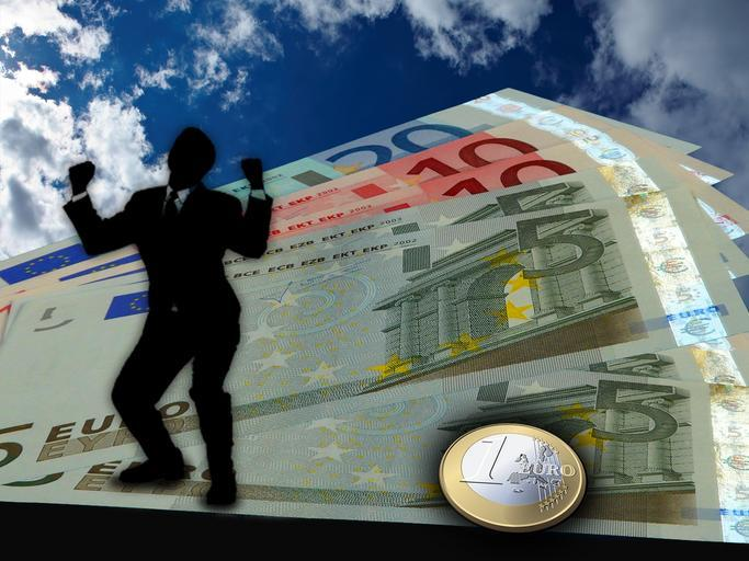 silueta člověka, radujícího se a stojícího na bankovkách